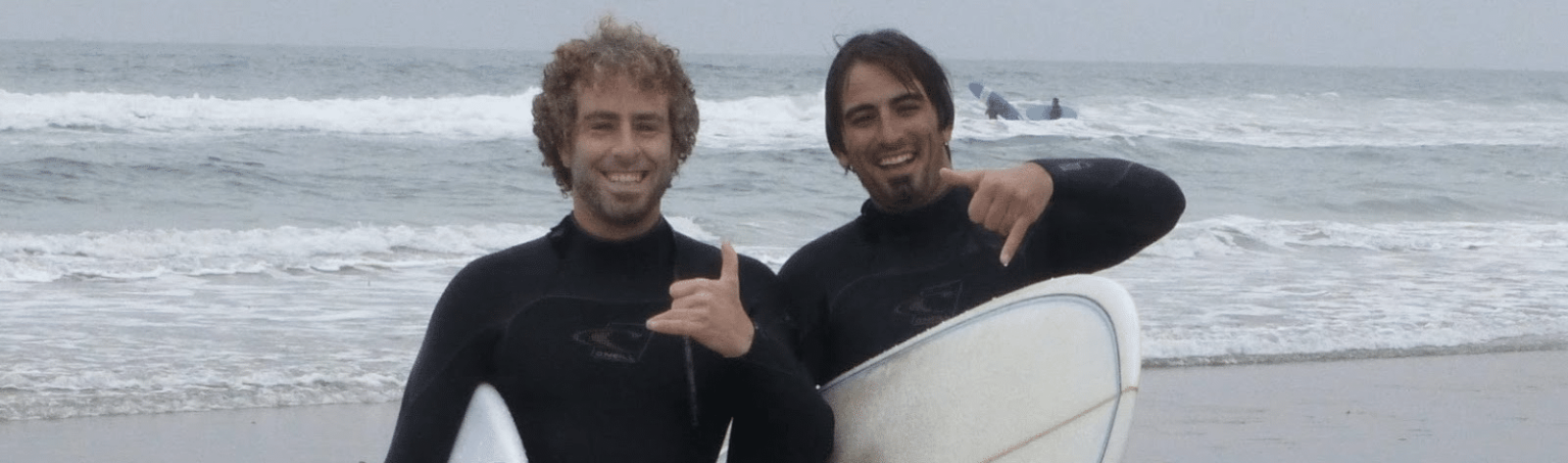 co-founders surfing with friend